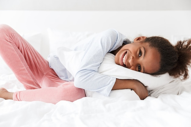 Süßes afroamerikanisches kleines mädchen, das zu hause lächelt und im bett liegt?