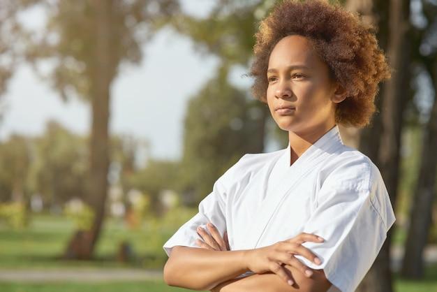 Süßes afroamerikanisches mädchen karateka, das auf der straße steht
