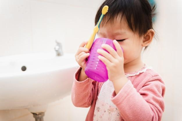 Süßes asiatisches kinderkleines mädchen, das ihre zähne im badezimmer putzt