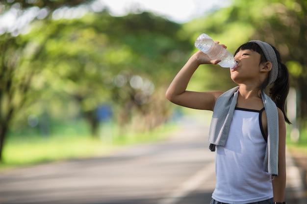 Süßes asiatisches mädchen trinkt wasser aus einer flasche im freien mit sonnenlicht