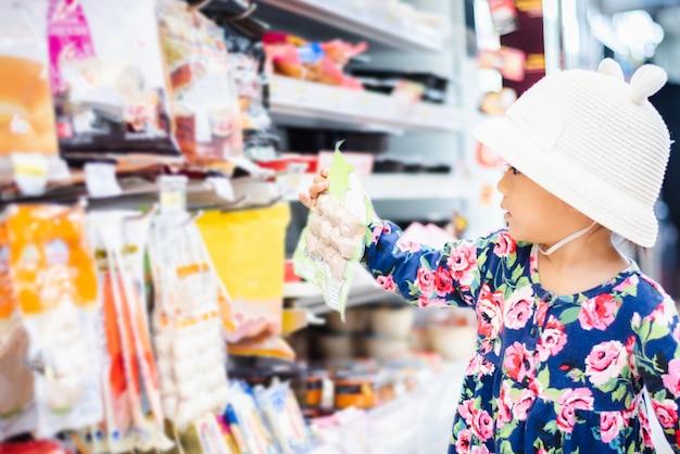 Süßes asiatisches mädcheneinkaufen im minimarkt mit korb, genießen, sache im handelszentrum zu kaufen