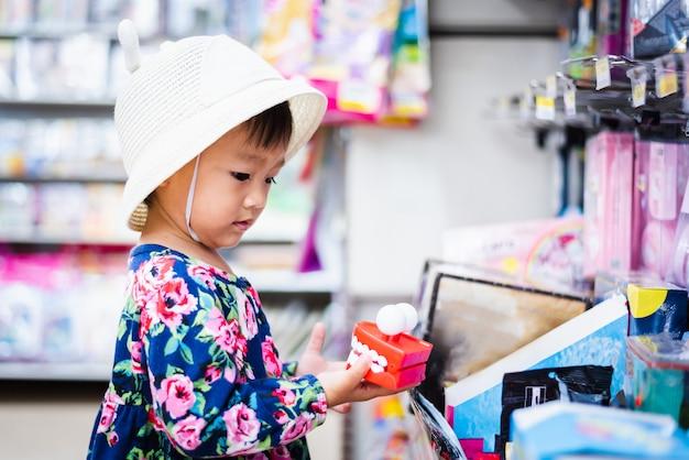 Süßes asiatisches mädcheneinkaufen im minimarkt mit korb, kleines spielzeug in ihrer hand betrachtend