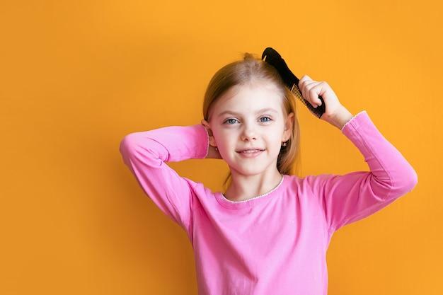 Süßes baby, baby 6-8 jahre alt kämmt ihr weiches blondes haar mittellangen kamm und lächelt auf einer orangefarbenen wand
