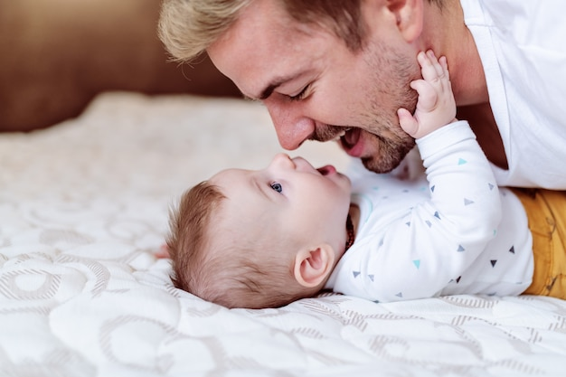 Süßes baby, das auf bett liegt und mit seinem vater spielt.