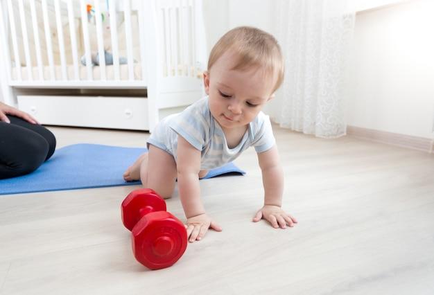 Süßes baby, das auf dem boden krabbelt und mit hanteln spielt playing
