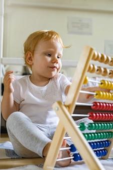 Süßes baby, das bunten abakus mit holzperlen spielt, kinderspielzeug, das ein selbstlernendes spiel genießt