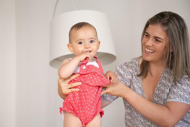 Süßes baby, das roten körper trägt, mit mutterunterstützung stehend, hand und tuchteil beißend, lächelnd, a. mittlerer schuss. elternschafts- und kindheitskonzept