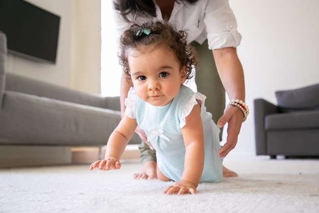 Süßes baby, das zu hause auf dem boden kriecht, hände der mutter, die kind in arme nimmt. elternschafts- und kindheitskonzept
