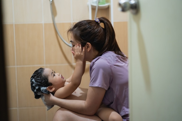 Süßes baby duscht mit ihrer mutter auf der toilette