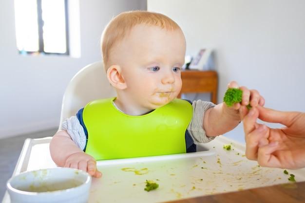 Süßes baby im lätzchen, das brokkoli-stück von mutter nimmt