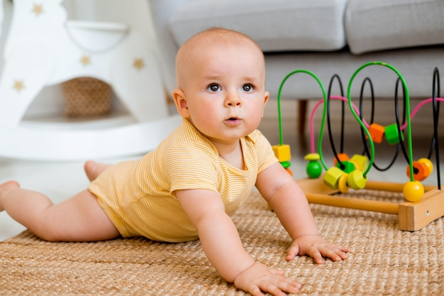 Süßes baby in einem gelben body spielt mit einem lernspielzeug