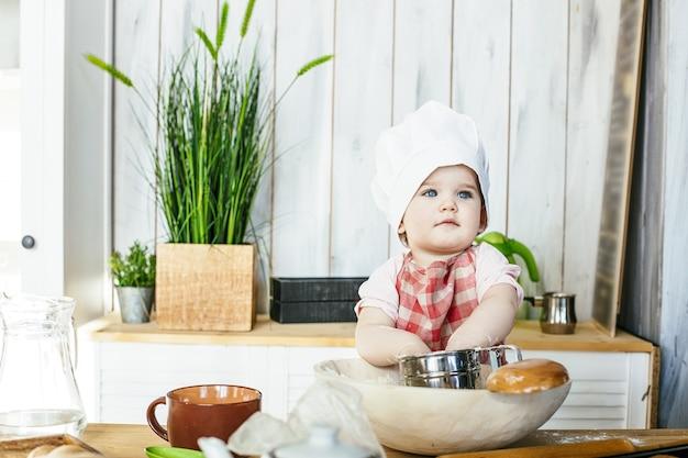 Süßes baby in einer mütze und schürze glücklich und gutaussehend, das gebäck und mehl in der küche zu hause zubereitet