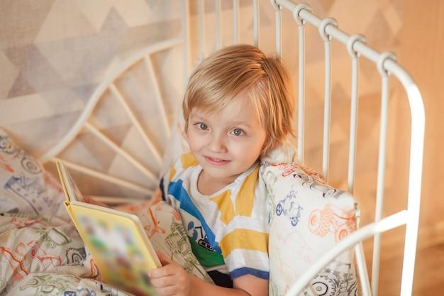 Süßes baby liegt im bett und liest ein buch.
