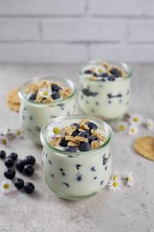 Süßes blätterteigdessert in einem glas mit frischen blaubeeren, schlagsahne, mascarpone, hüttenkäse und keksplätzchen oder waffeln auf hellem hintergrund.