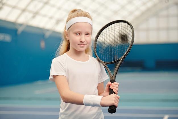 Süßes blondes kleines mädchen in weißer activewear, das tennisschläger an der linken schulter hält, während es in stadionumgebung vor der kamera steht