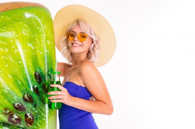 Süßes blondes mädchen in einem badeanzug mit brille und mit einer kiwi kühlen matratze