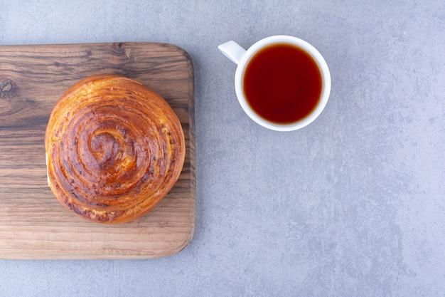 Süßes brötchen auf einem brett neben einer tasse tee auf marmoroberfläche