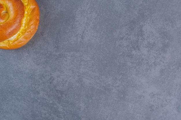Süßes brötchen, das aufrecht auf marmorhintergrund steht. foto in hoher qualität