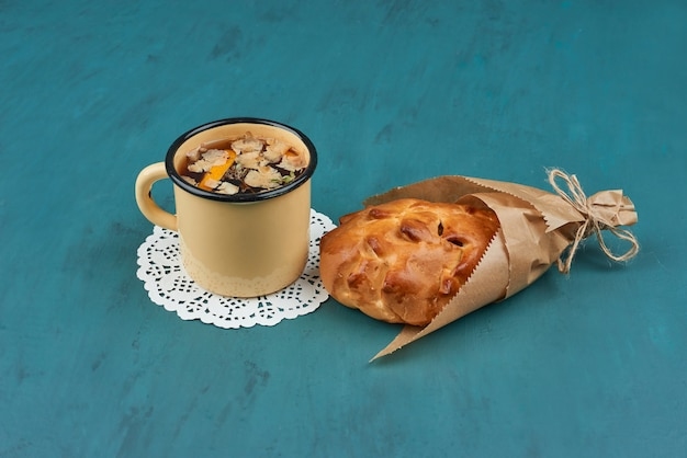 Süßes brötchen mit einer tasse kräutertee.