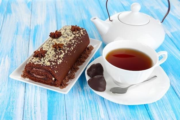 Süßes brötchen mit einer tasse tee auf dem tisch