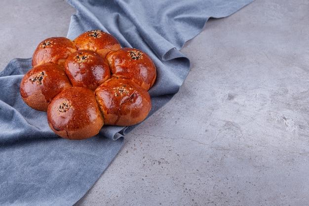 Süßes brötchen mit sesam auf steinhintergrund gelegt.