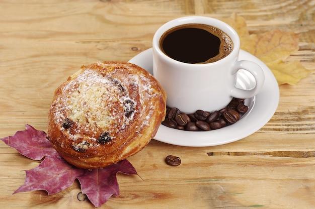 Süßes brötchen und kaffeetasse auf altem holztisch