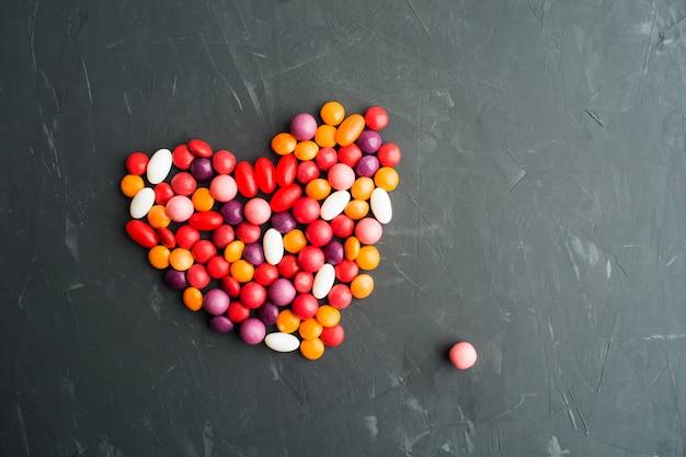 Süßes buntes süßigkeitsherz über grauem hintergrund