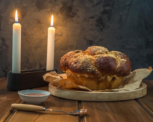 Süßes challah-brot auf einer bewaldeten runden platte auf hölzerner brauner tabelle mit honig und zwei kerzen an dem shabbat-abend, der kidush macht