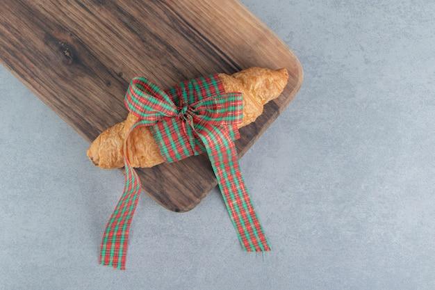 Süßes croissant auf tablett, auf dem marmorhintergrund. hochwertiges foto