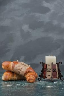 Süßes croissant mit kerze auf marmorhintergrund.
