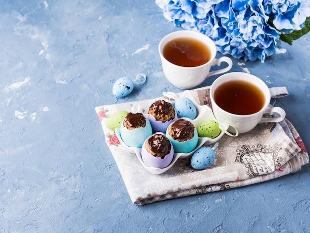 Süßes cup ostern backt treets in den bunten eierschalen auf blau zusammen
