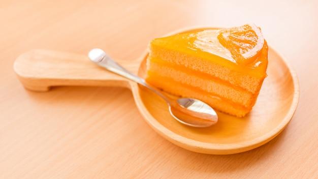 Süßes dessert des orangenkuchens in der holzteller auf holztisch