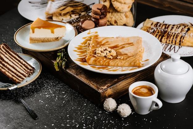 Süßes dessert von pfannkuchen und kuchen in der zusammensetzung auf schwarz