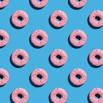 Süßes donutmuster auf einem blauen hintergrund.