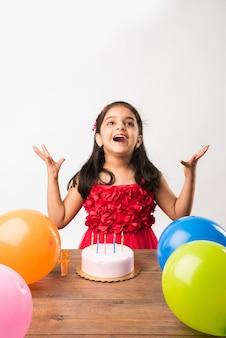 Süßes entzückendes kleines indisches oder asiatisches kleines mädchen, das geburtstag feiert, während es erdbeerkuchen hält und kerzen am tisch bläst oder isoliert auf weißem oder rotem hintergrund steht