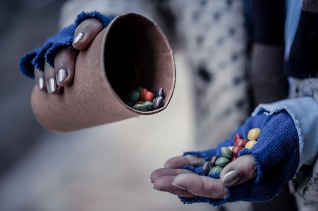 Süßes essen. nahaufnahme einer hand einer armen obdachlosen frau, die mit süßigkeiten gefüllt wird