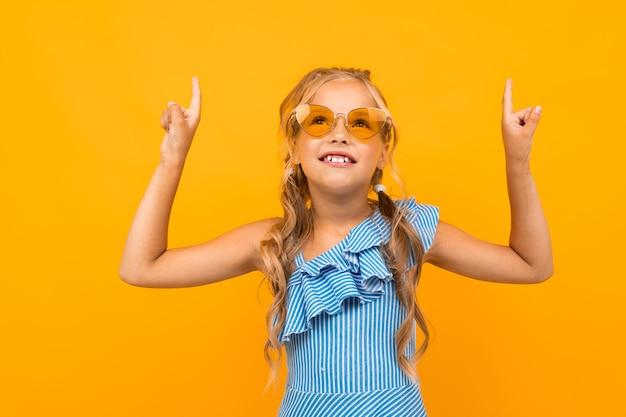 Süßes europäisches mädchen in der hellen sonnenbrille zeigt finger auf einer gelben wand