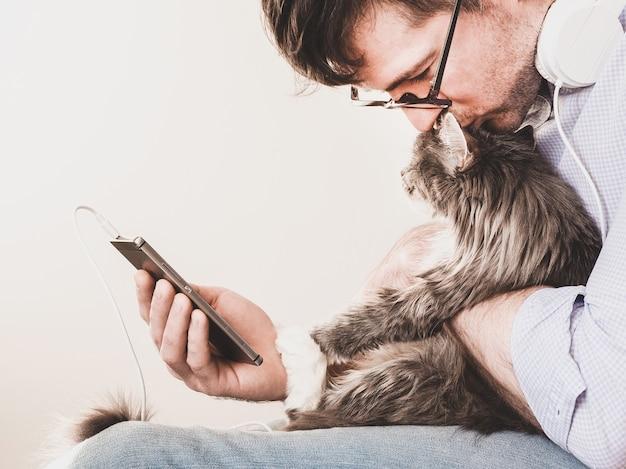Süßes, flauschiges kätzchen und ein mann mit einem telefon. haustierpflegekonzept
