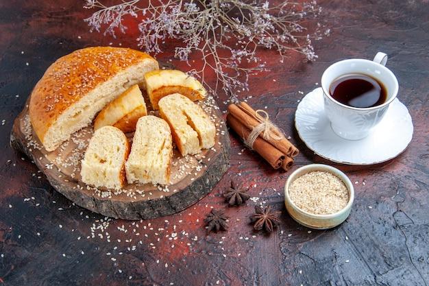 Süßes gebäck der vorderansicht, das in stücke mit tasse tee auf dunklem hintergrund geschnitten wird