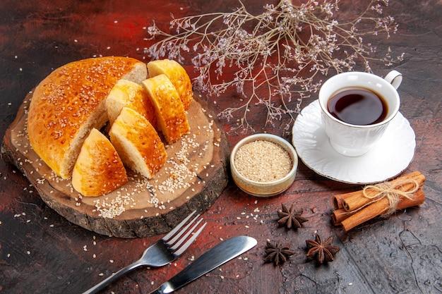 Süßes gebäck der vorderansicht, das in stücke mit tee auf dunklem hintergrund geschnitten wird