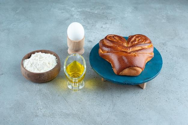 Süßes gebäck, mehl und olivenöl auf marmoroberfläche.