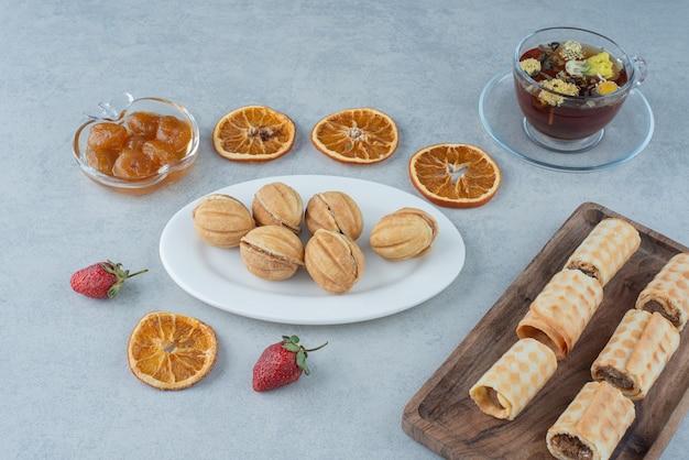 Süßes gebäck mit getrockneter orange und tasse kräutertee auf marmorhintergrund. hochwertiges foto