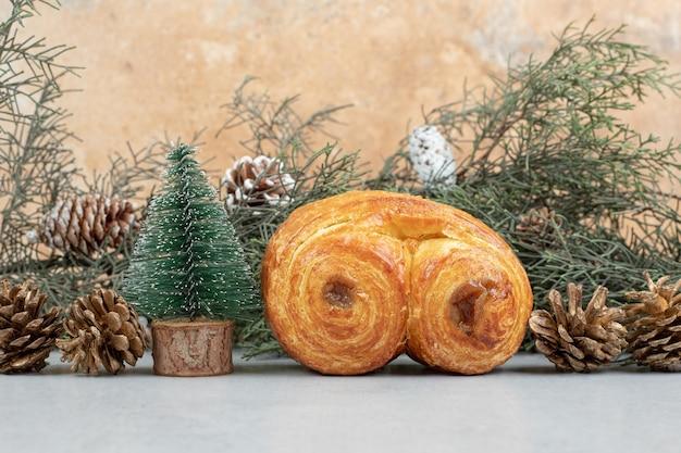 Süßes gebäck mit tannenzapfen und weihnachtsbaum.