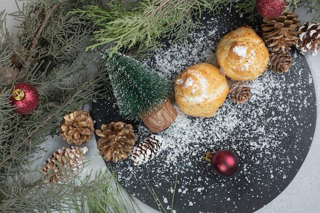 Süßes gebäck mit tannenzapfen und weihnachtsbaum
