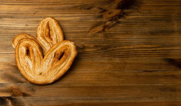 Süßes geflochtenes palmiersgebäck, palmenherz oder elefantenohr auf hölzernem tischschreibtischhintergrund. französische blätterteig- oder pastetenfeuilletee-draufsicht mit kopierraum