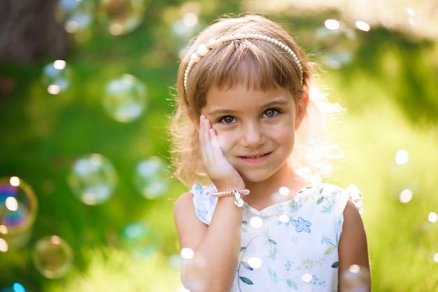 Süßes, glückliches, lächelndes fünfjähriges mädchen, das auf einem gras liegt
