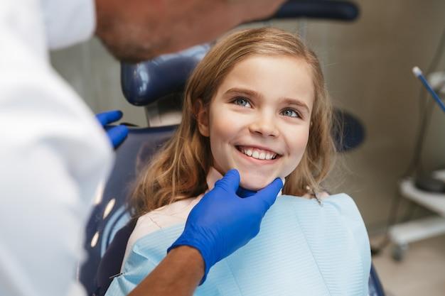 Süßes glückliches schönes kindermädchen, das im medizinischen zahnarztzentrum sitzt und kamera betrachtet.