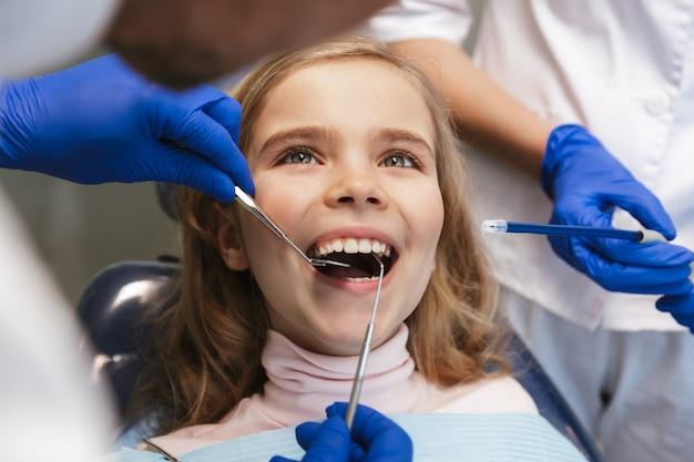 Süßes glückliches schönes kindermädchen, das im medizinischen zahnarztzentrum sitzt
