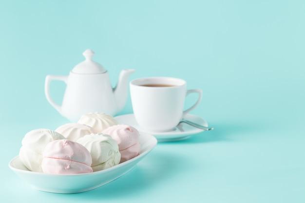 Süßes hausgemachtes dessert - beeren-marshmallow (zephyr) auf einem einfachen aquamarinhintergrund