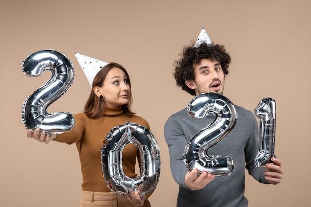 Süßes junges paar tragen neujahrshut posiert für kamera mädchen zeigt und und kerl mit und auf grau